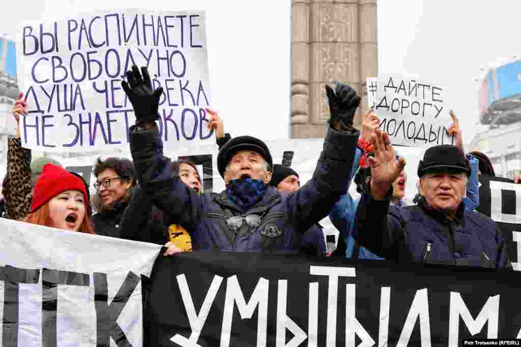 """Protestors chant in front of Almaty's Independence Monument. Chants included, """"Kazakhstan Without Nazarbaev"""" and, """"Old Man, Go Away!"""""""