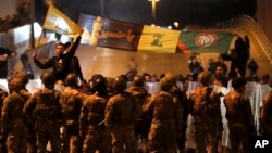 Supporters of the Iran-backed militant group hold the flags of Hezbollah and Amal Movement, as they stand in front of Lebanese army soldiers forming a barrier. November 25, 2019