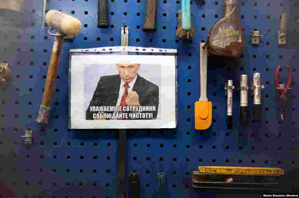 "A sign featuring Vladimir Putin saying ""Dear colleagues, keep clean,"" in a factory near Murmansk."