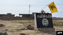 A flag of the Shi'ite Hizballah militant group flutters over a mural depicting the emblem of the Islamic State (IS) group in Al-Alam village, northeast of the Iraqi city of Tikrit, in early March.