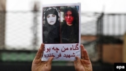 "An Afghan demonstrator holds a placard reading in Dari ""What was my sin?"" with a picture of Farkhunda Malikzada, who was brutally murdered by a mob, during a protest against her killing outside the Supreme Court in Kabul in March 2015."
