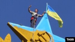A Moscow city worker takes a selfie while atop the Kotelnicheskaya Embankment building in Moscow to remove the Ukrainian flag mounted there overnight on August 19-20.