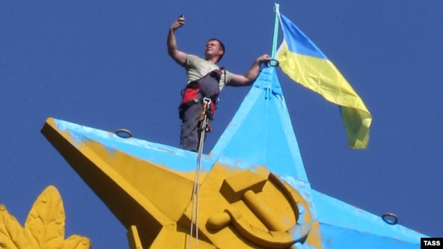 A Moscow city worker takes a selfie while atop the Kotelnicheskaya Embankment building in Moscow to remove the Ukrainian flag mounted there overnight on August 19-20. The hammer-and-sickled star and laurel wreath was also painted in Ukrainian colors.