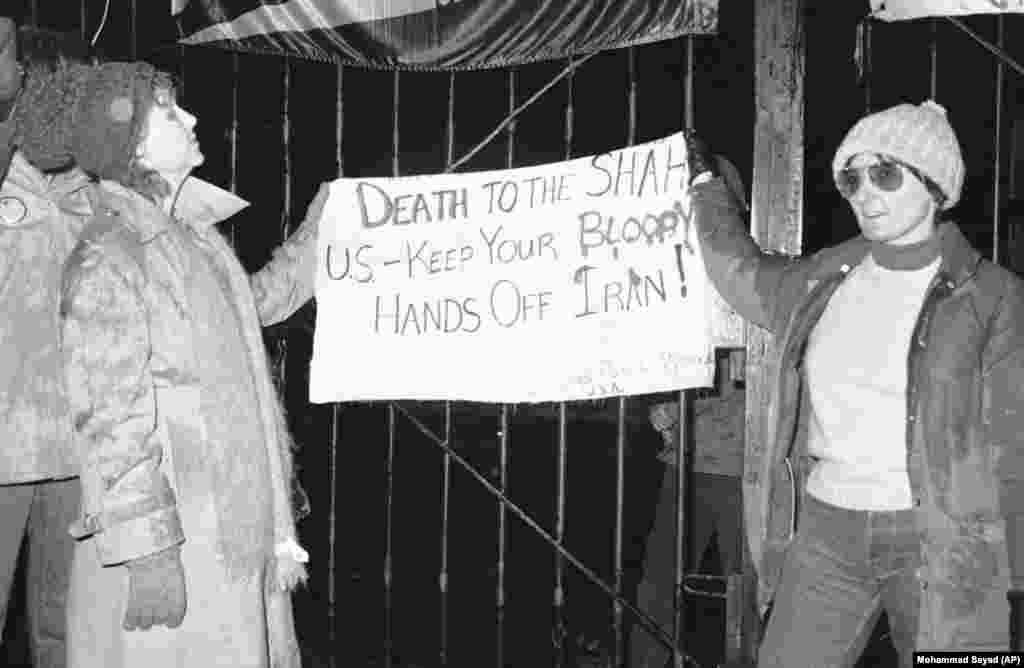 Некоторые граждане США симпатизировали иранским студентам: двое американцев, Кэрол Даунер (слева) из Лос-Анджелеса и Ребекка Чокер (справа) из Флориды, стоят у посольства США с плакатом с надписью: «Смерть шаху! США, уберите свои кровавые руки от Ирана». 15 декабря 1979 года.