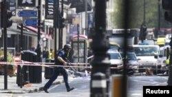 Лондон көшесінде жүрген қарулы полицей. Көрнекі сурет.