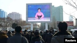Люди на вулиці Пхеньяна дивляться офіційну заяву про випробування, 6 січня 2016 року