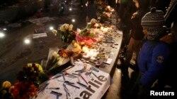Люди приносят цветы и зажигают свечи в память о жертвах нападений. Париж, 10 января 2015 года.