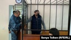 Обвиняемый в поддержке запрещенного в Казахстане движения «Демократический выбор Казахстана» (ДВК) Серик Жахин (в центре) в суде по его делу. 16 сентября 2019 года.
