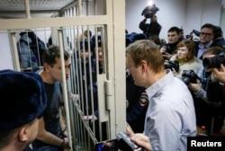 Олексій Навальний (праворуч) спілкується зі своїм братом Олегом крізь грати в залі суду в Москві, 30 грудня 2014 року