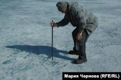Житель поселка Вячеслав Максимов показывает, какие промоины во льду Байкала опасны