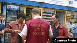 Россия - Российский чиновник проверяет документы мигрантов (архив)