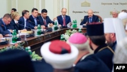 Acting Ukrainian President Oleksandr Turchynov (right) speaks, flanked by Prime Minister Arseniy Yatsenyuk (center), during the opening of roundtable talks on Ukraine's deepening crisis in Kyiv on May 14.
