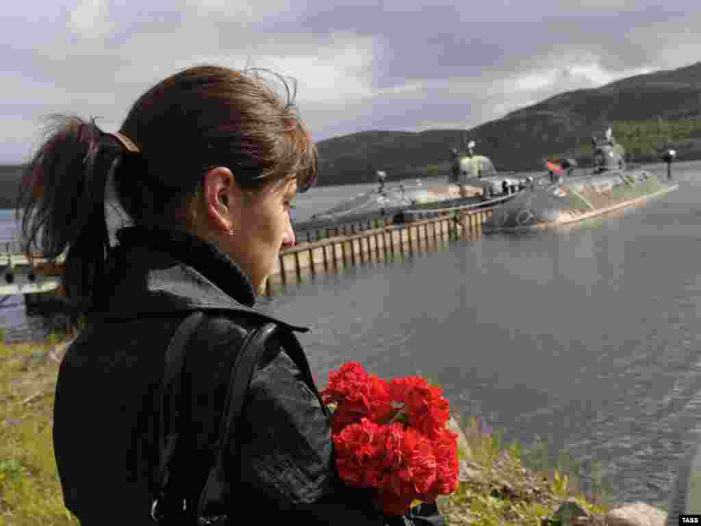 "A woman mourns during memorial ceremonies on August 12 to commemorate the 10th anniversary of the ""Kursk"" nuclear submarine disaster, in the submarine's home base of Vidyayevo. Photo by Lev Fedoseyev for ITAR-TASS"