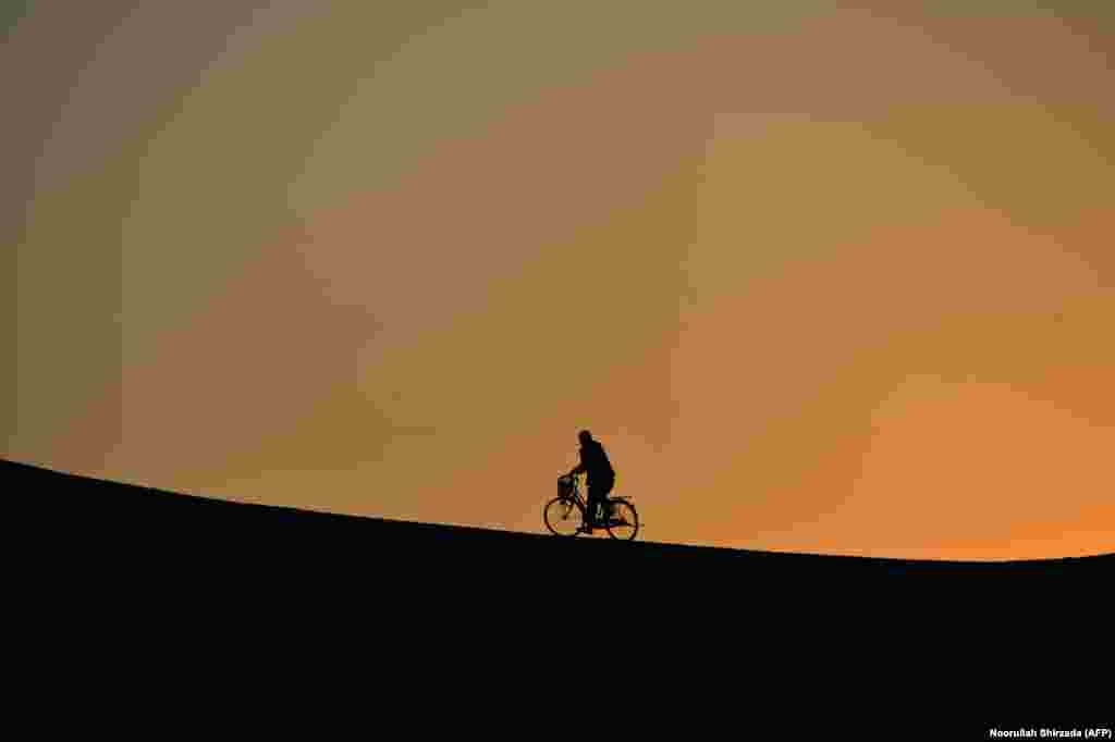 An Afghan man rides a bicycle up a a hill during sunset in Jalalabad. (AFP/Noorullah Naftoon)