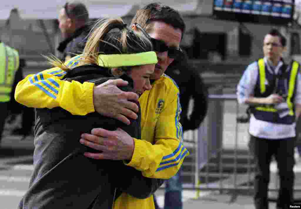 A woman is comforted by a man near a triage tent after explosions went off at the 117th Boston Marathon.