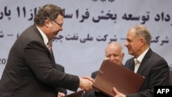 Patrick Pouyanne (left), chairman and CEO of the French energy company Total, shakes hands with Ezzatollah Akbari, managing director of the Petropars Group, after signing an offshore gas field agreement in Tehran on July 3.