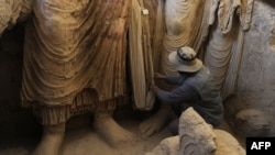 An archaeologist looks at the remains of Buddha statues discovered inside an ancient monastery in Mes Aynak in Afghanistan's eastern province of Logar.