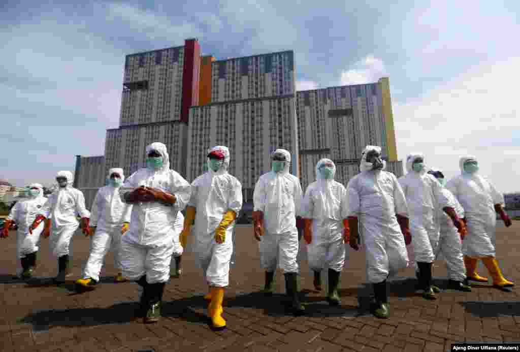 Indonesian Red Cross Society personnel walk in protective suits during an operation to spray disinfectant at the Kemayoran Athletes Village, to prevent the spread of coronavirus disease (COVID-19) in Jakarta, Indonesia