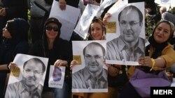 Під час виборчої кампанії в Ірані прихильники тримають плакати з зображенням кандидата Могаммада Багера Галібафа