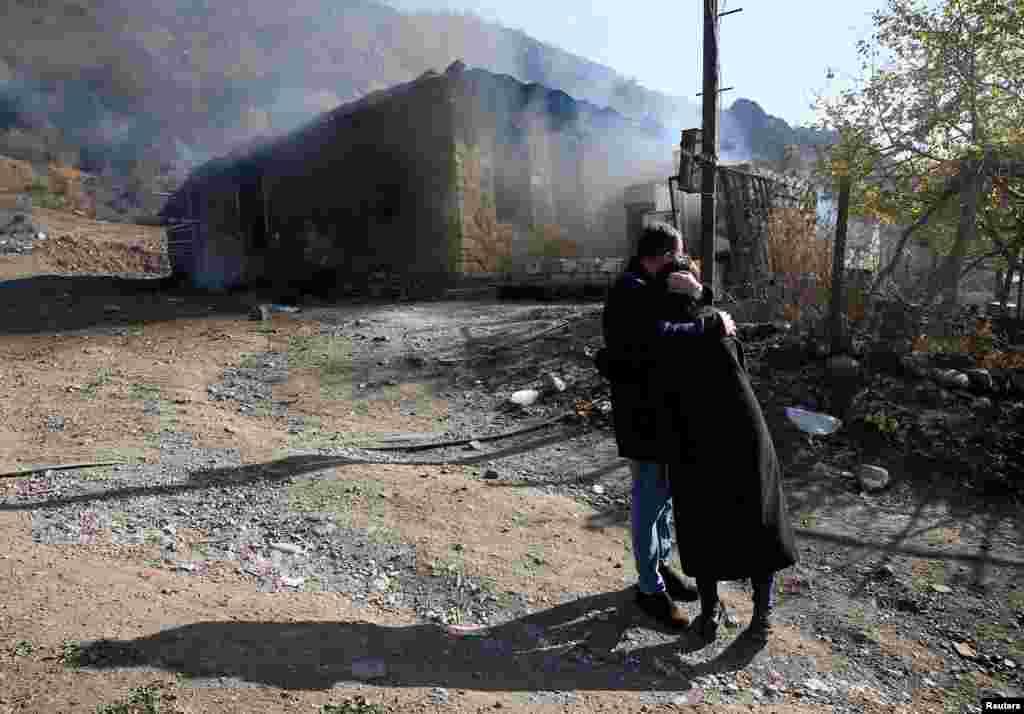 Армянская пара обнимается, наблюдая, как горит их дом в Чаректаре (Чарактаре)