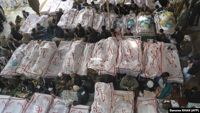Pakistani Shi'ite Muslims gather around the coffins of the bombing victims as they demonstrate in Quetta on February 18.