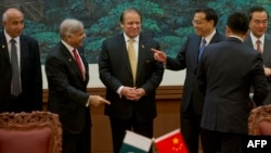 Chinese Premier Li Keqiang (third from right) gestures near Pakistani Prime Minister Nawaz Sharif (center) and Punjab Chief Minister Shahbaz Sharif (second from left) before a signing ceremony at the Great Hall of the People in Beijing on July 5.