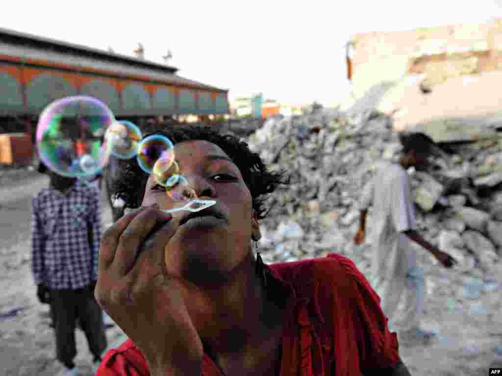 Прастытутка на вуліцы Порт-о-Прэнсу пускае бурбалкі - Фота: AFP