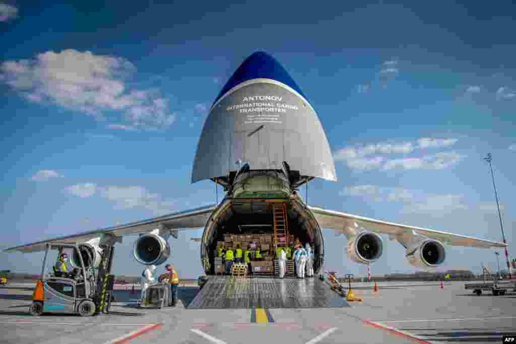 Сотрудники аэропорта в Будапеште разгружают самолет с медицинскими масками и другим оборудованием для борьбы с коронавирусом, Венгрия. 4 апреля 2020 года