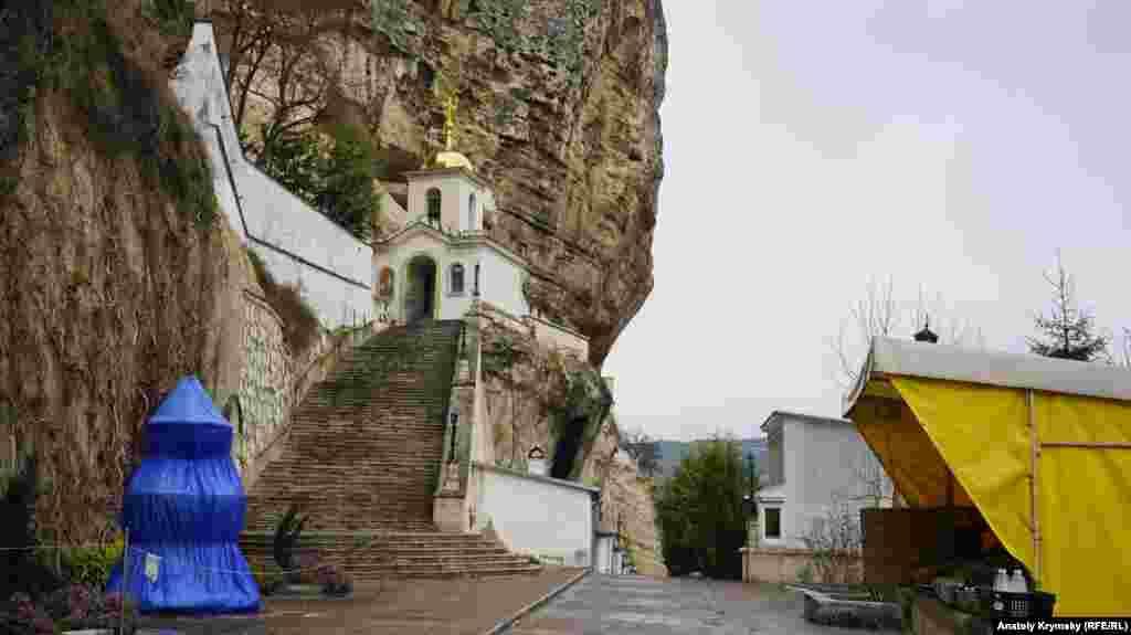 Фонтан (слева) у лестницы, ведущей к звоннице и пещерной Успенской церкви не работает и обтянут пленкой. Продолжает работать монастырская лавка (справа)