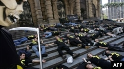 As part of a commemorative demonstration, activists from the environmental group Greenpeace lie on the stairs of the municipal theatre in the Brazilian city of Goiania, where a notorious radioactive accident resulted in the deaths of four people and affected thousands of others nearly 30 years ago. (file photo)