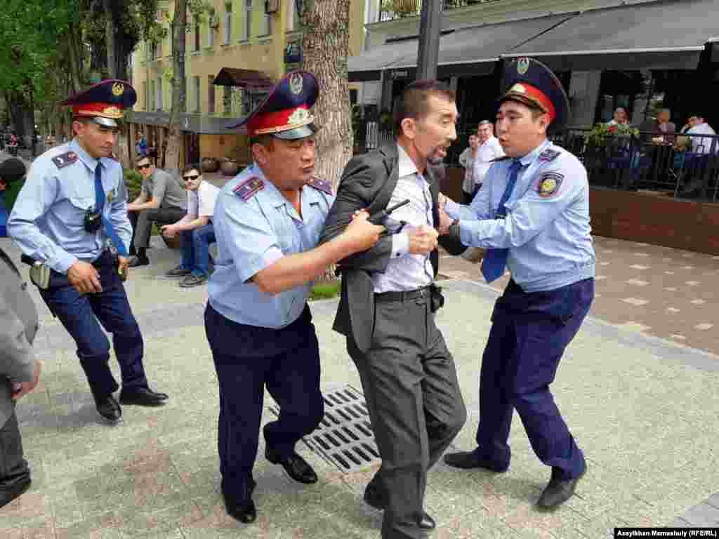 Наразылық акциясына шыққандардың бірін полиция қызметкерлері ұстап жатыр.