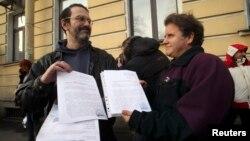 Дмитро Литвинов і Пітер Вілкокс демонструють постанови про закриття справи