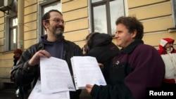 Greenpeace өкілдері Дмитрий Литвинов пен Питер Уилкокс қылмыстық істерінің жабылғаны туралы сот шешімін ұстап тұр. Санкт-Петербург, 25 желтоқсан 2013 жыл.
