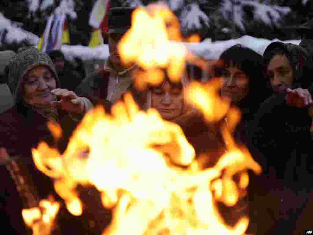 Supporters of South Ossetian presidential candidate Alla Dzhioyeva warm up near a fire during a rally in Tskhinvali after the November 27 vote was annulled by the breakaway Georgian republic's courts. (AFP Photo/ Mikhail Mordasov)