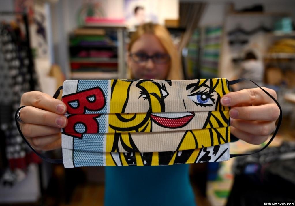 Женщина показывает защитную маску для лица, сделанную хорватским дизайнером Зораном Араговичем.