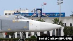 A Russian Su-24 bomber passes by a portrait of Syrian President Bashar al-Assad at the Hmeimim military base.