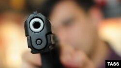 Russia -- man pointing a gun at the camera at Mir Okhoty sportsman gun shop, 23Apr2013