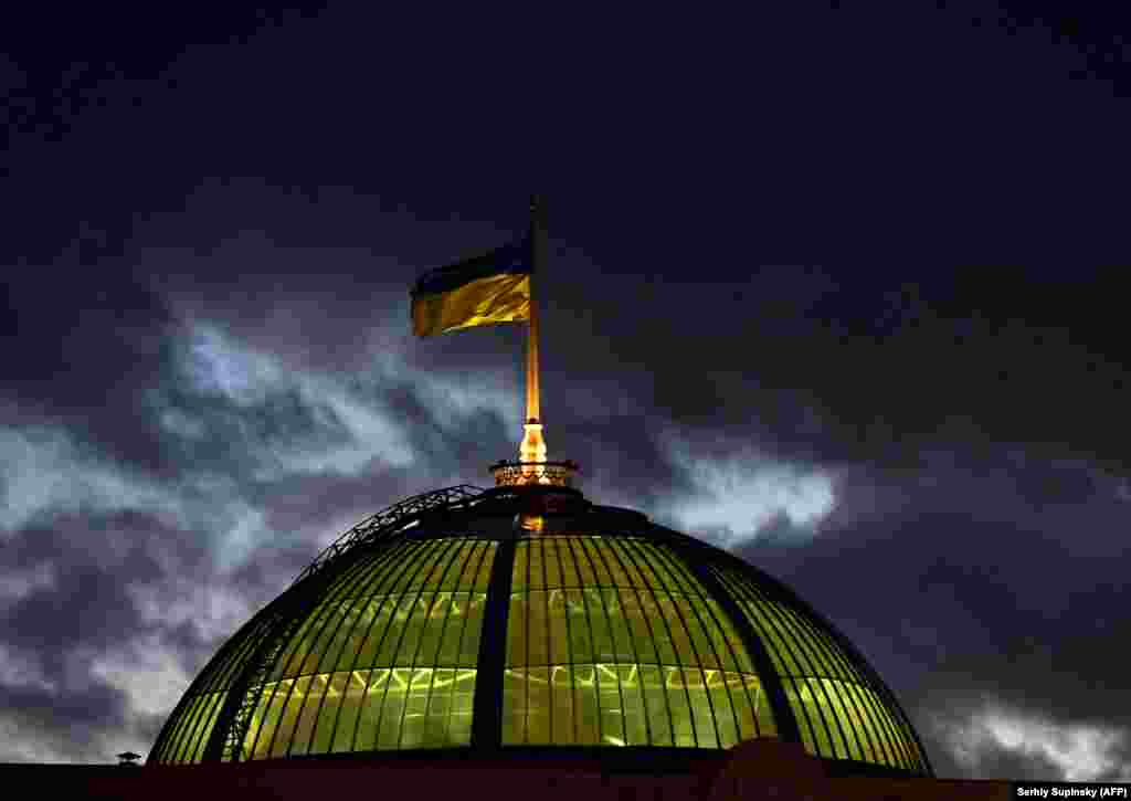 A Ukrainian flag flies in the wind on top of the parliament building in Kyiv. (AFP/Sergei Supinsky)