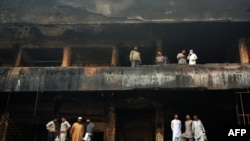 Pakistani shopkeepers stand on the balconies of their shops in a burned-out market in Karachi on December 30.