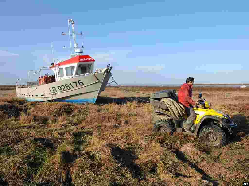 Последствия урагана во Франции. Выброшенный на берег рыбацкий катер.