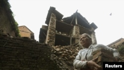 Женщина, пострадавшая от землетрясения, собирает обломки своего дома. Непал, 19 сентября 2011 года.
