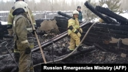 Сотрудники МЧС России на месте сгоревшего помещения на территории лесопилки в Томской области. 21 января 2020 года.