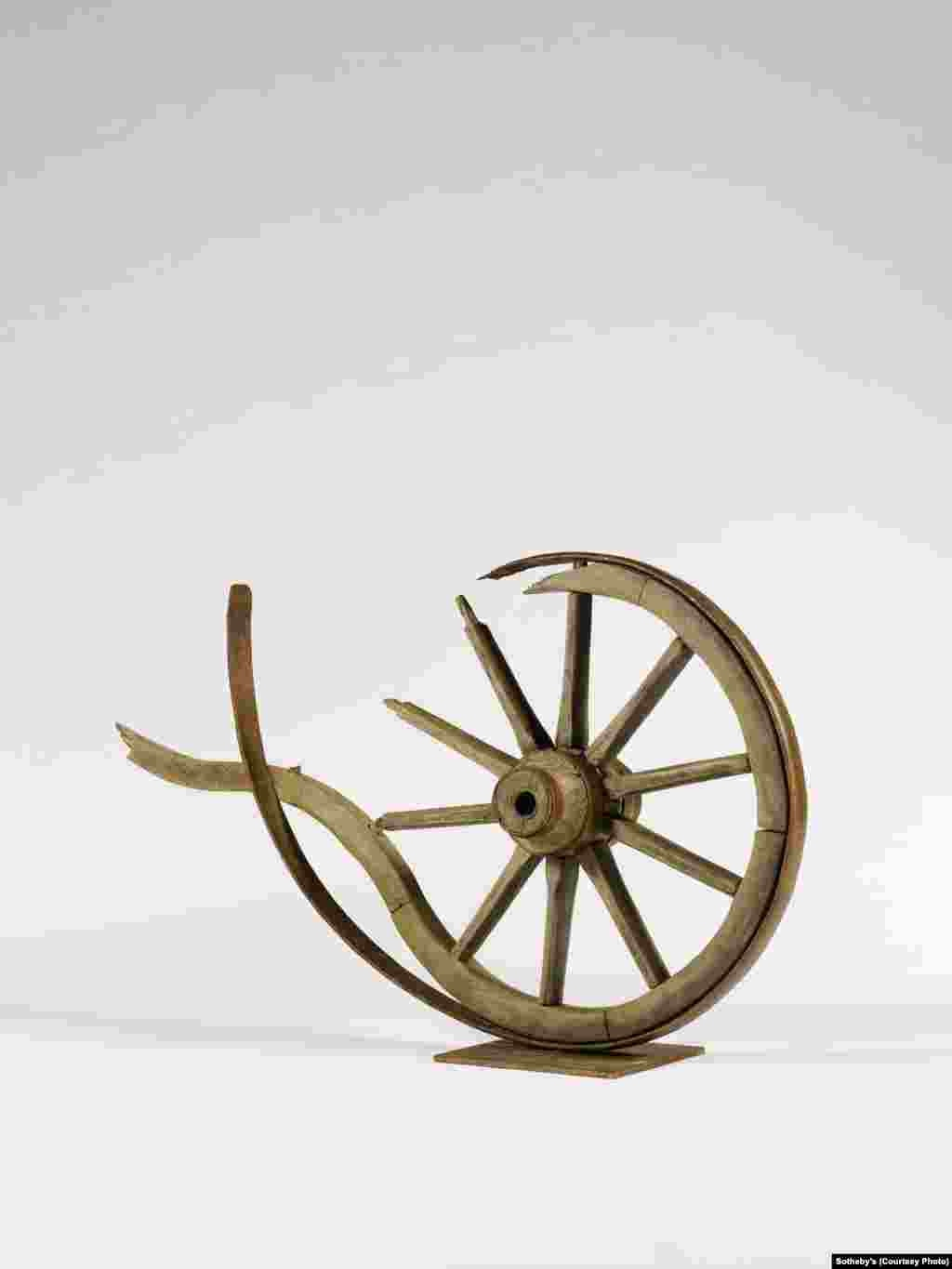 """Disintegration,"" a 2012 wood and metal sculpture by Armenian artist Armen Gevorgyan (b. 1958). The broken wheel is symbolic of the Armenian people's long history of resettlement."