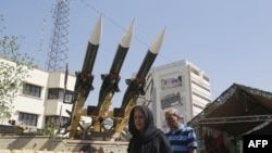 Iranians walk past Sam-6 missiles displayed in the street during a commemoration of the 1980-88 Iran-Iraq war, south of Tehran on September 26, 2016.