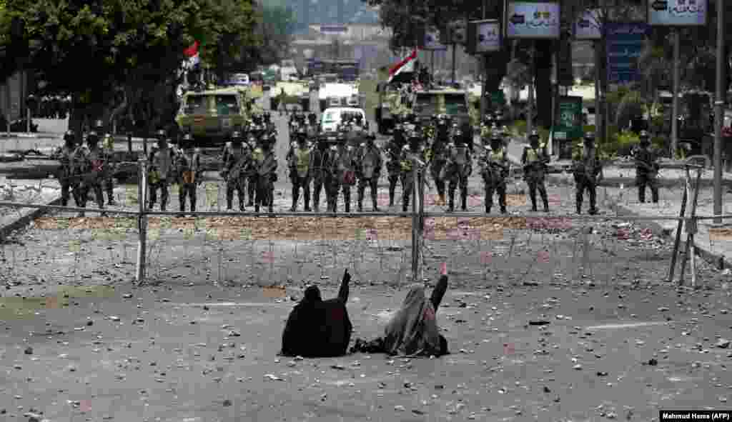 Egyptian supporters of deposed President Muhammad Morsi sit in front of barbed-wire fencing set up to block access to the headquarters of the Republican Guard in Cairo. (AFP/Mahmud Hams)