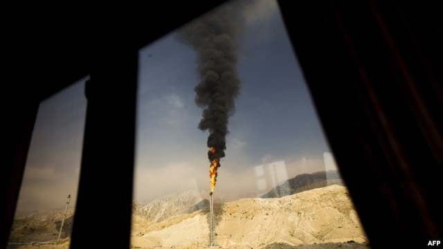 A gas flame is seen through a bus window at the South Pars gas field facilities in Iran's southern port of Assaluyeh.