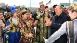 Нурсултан Назарбаев в бытность президентом Казахстана в окружении одетых в национальные костюмы людей на мероприятии в столице в День единства народа Казахстана. 1 мая 2018 года.