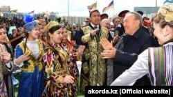 Президент Казахстана Нурсултан Назарбаев в окружении одетых в национальные костюмы людей на мероприятии в Астане в День единства народа Казахстана. 1 мая 2018 года.