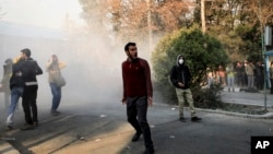 Protesters in Tehran react as a smoke grenade is thrown by Iranian police near the city's university last week. The Islamic Revolutionary Guards Corps says it has now quashed the unrest in the country which it blamed on foreign interference.