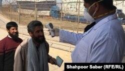 بررسی وضعیت صحی مسافرانی که از ایران وارد افغانستان میشوند توسط کارمندان صحی در اسلام قلعه.
